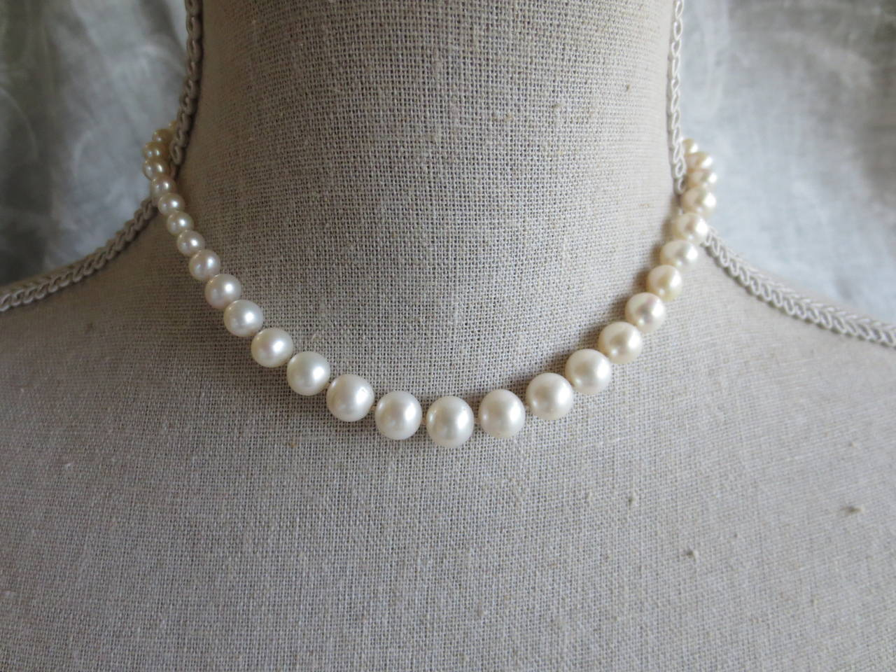 "A classic necklace made of cultured pearls. Each pearl is hand selected for its size to create an absolutely detailed and perfectly graduated necklace. Beads measure from 6.5 to 2.5 mm. This necklace measures 15"" in length, and sits perfectly"