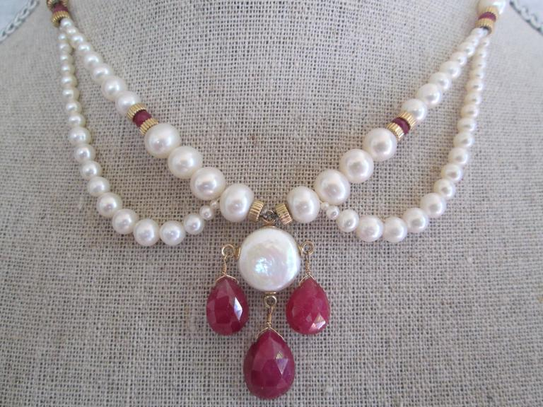 Uniquely graduated pearl necklace with ruby briolettes attached with 14k yellow gold findings, beads, and clasp. Centerpiece his highlighted by round, coin pearl. Lightweight, and graceful. Great for weddings, graduations, and other formal