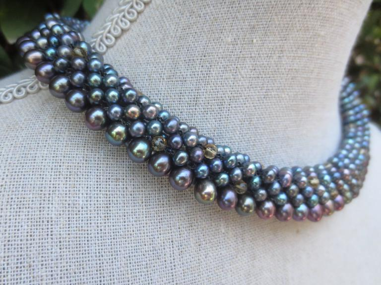 Black pearl and faceted Citrine beads are woven together to create a rope style necklace. The beads measure 3.5mm each in addition to the larger, teardrop black pearls, and woven into a tubular rope of approximately an inch thick. This modern and