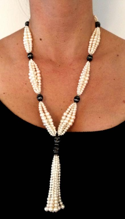 This elegant sautoir features double graduated white pearl clusters strung between  wooded beads detailed with silver inlay. The contrast between the white pearls and the dark wood beads is highlighted by fine 14 k white gold beads.  Tassel measures