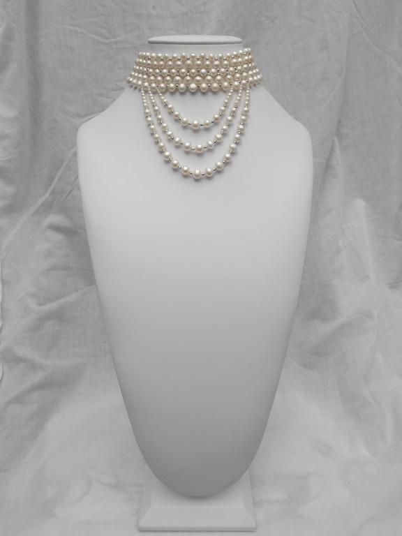 This striking draped choker features 5mm- 7mm white pearls beautifully woven with rhodium-plated silver faceted beads, and completed with a rhodium silver clasp. Emerging from the choker, are three elegant graduated white pearl and white gold