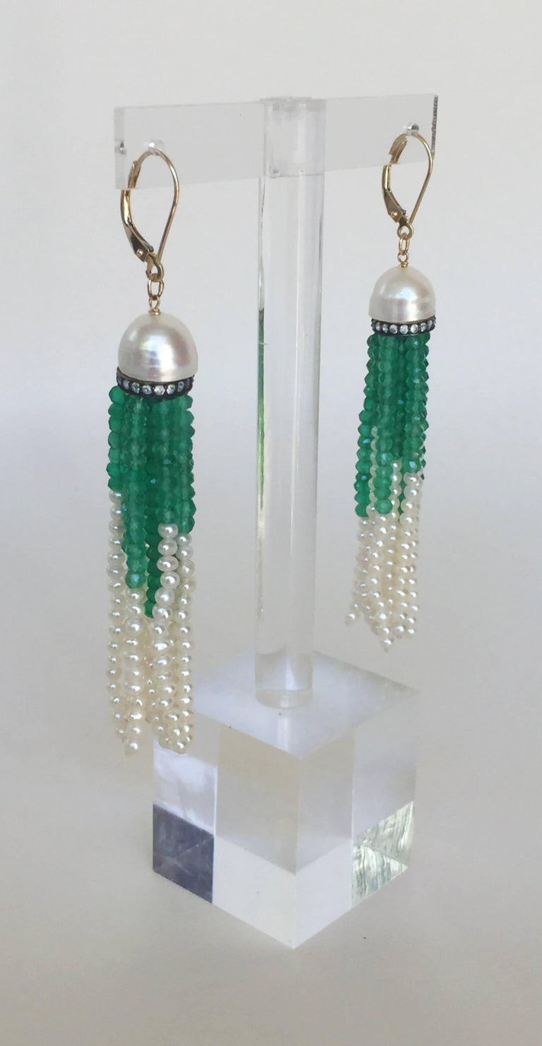 These dazzling tassel earrings start with a large half pearl sitting atop a diamond encrusted cup. Vibrant green onyx and small pearl strands complete the earrings. The lever back closure is made of 14k yellow gold. They hang around 3 inches to