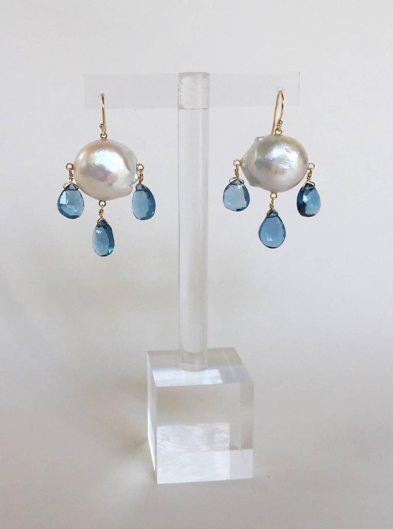 Three London blue topaz droplets hang from a large round Baroque white pearl, by a 14k yellow gold hook and wiring. They hang perfectly at 1.65 inches. These beautiful and bold earrings add a graceful touch to your outfit.