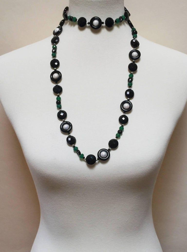 This sautoir is composed of green and black faceted onyx beads with round white pearls and 14k white gold faceted beads. The differing shapes and texture of the beads allows the necklace to flow elegantly and shine brilliantly. The necklace hangs at