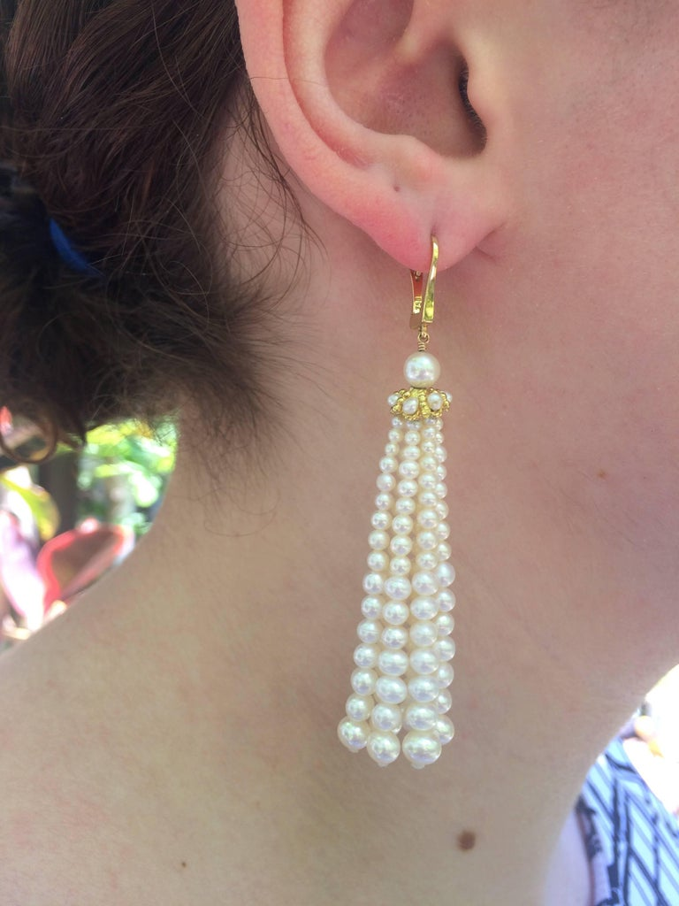 Graduated fine cultured pearl earrings measures 3 inches from top of ear wire. Pearl strands hang from yellow gold cups detailed with pearls. 14 k yellow gold ear wires.