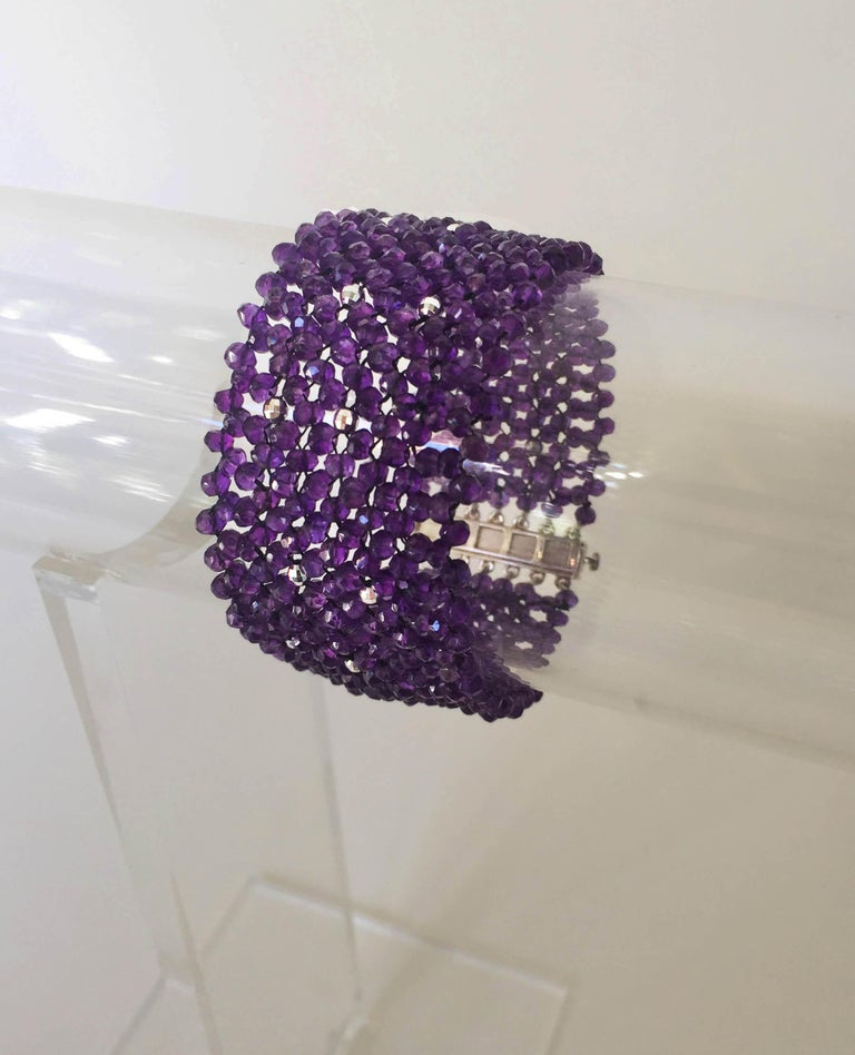 The woven faceted amethyst cuff bracelet with sterling silver clasp and beads is a beautiful shade of deep purple. At 1.25 inches wide and 7.15 inches long this bracelet gracefully drapes the wrist. The rhodium plated silver beads twinkle throughout