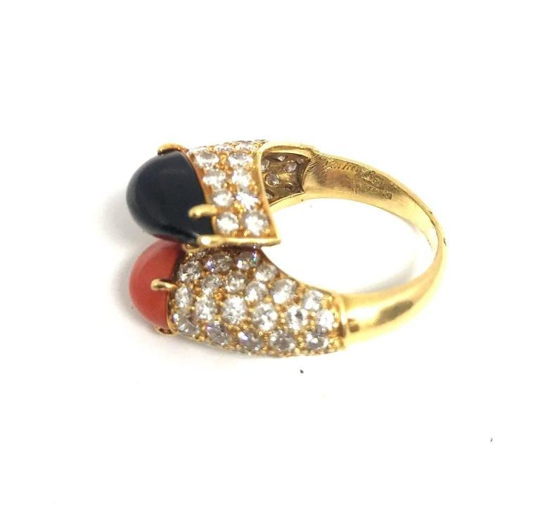 This wonderful vintage diamond ring features orange coral and onyx cabochons. Sophisticated yet classic this ring would complement any casual look or would look amazing at a cocktail party.The ring is signed by Cartier and there is approximately