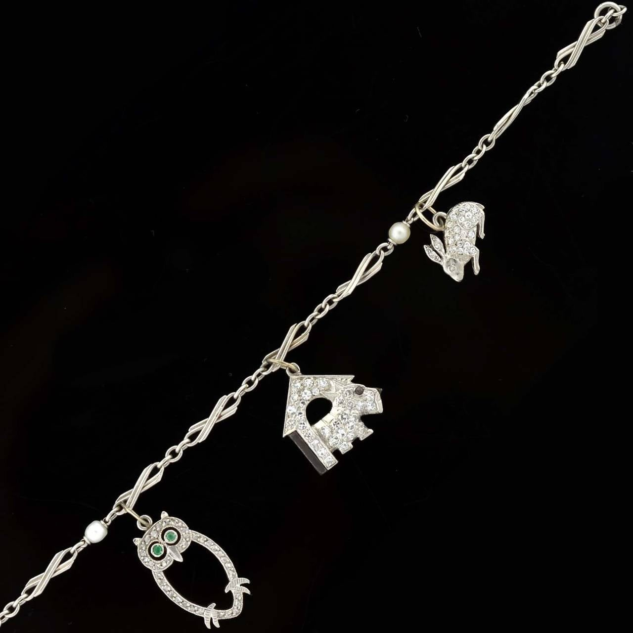 A beautiful charm bracelet from the Art Deco (ca1920) era! This lovely piece is a wonderful compilation of 5 charms which dangle from a fine platinum and pearl chain bracelet. Each charm is unique and all are detailed with a sparkling diamond
