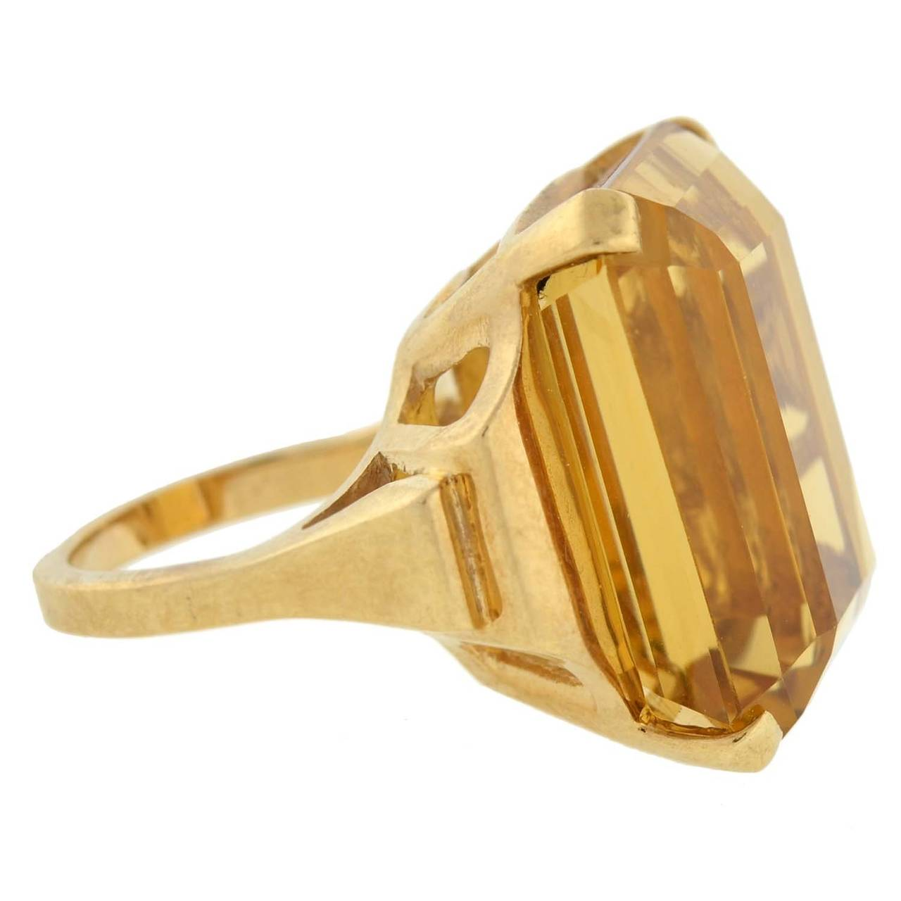 A magnificent citrine ring from the Retro (ca1940) era! This incredibly fabulous piece is made of 14kt yellow gold and holds a large faceted citrine stone at its center. The large stone, which is prong set, weighs approximately 30ct and displays a