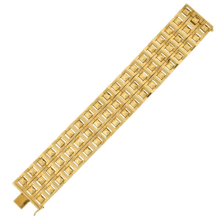This fabulous estate bracelet makes a very stylish, modern statement piece! Crafted in 14kt yellow gold, it has a substantial appearance formed by rows of hinged links. A pattern of pyramid-shaped studs rest in between open squares, giving a