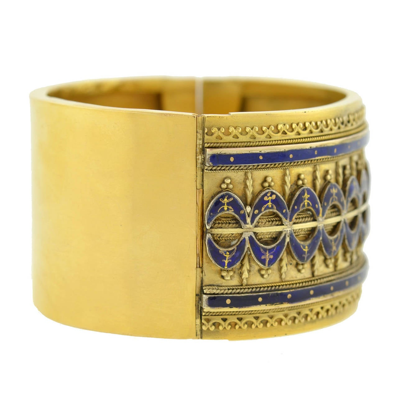 A gorgeous Etruscan bracelet from the Victorian (ca1880) era! This wide bangle is made of vibrant 15kt yellow gold (indicating English origin) and has a fantastic 3-dimensional design that adorns the front surface. The face of the bracelet is