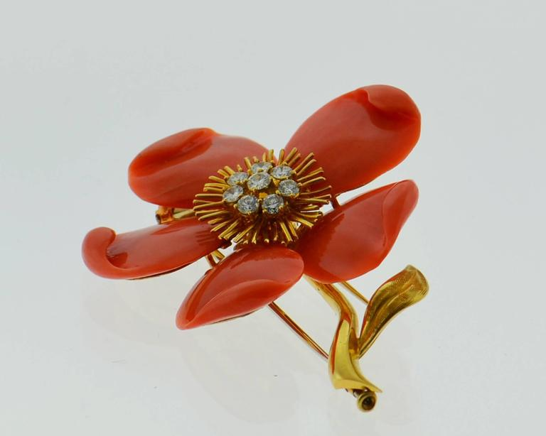 Designed as a flower this chic Brooch from world famous designer Van Cleef & Arpels features Mediterranean  Coral and Diamonds. The brooch has 8 round-cut diamonds with an approximate total weight  of .65 carats. Diamond are from E to F colors and