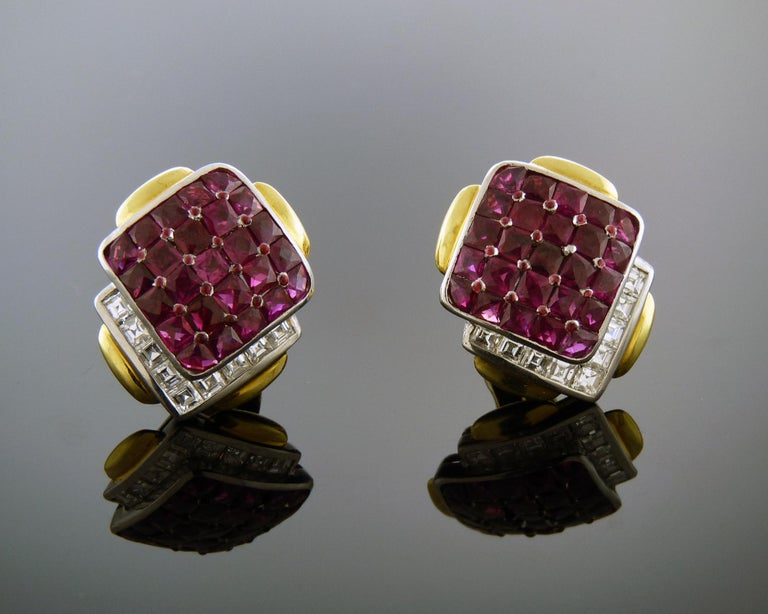 A stunning pair of David Webb clip-on earrings featuring approximately 10.62 carats of calibre-cut rubies, and 2.16 carats of square-cut diamonds, set in platinum and 18K gold. Accompanied by Certificate of Authenticity dated August 09, 2018.  Style