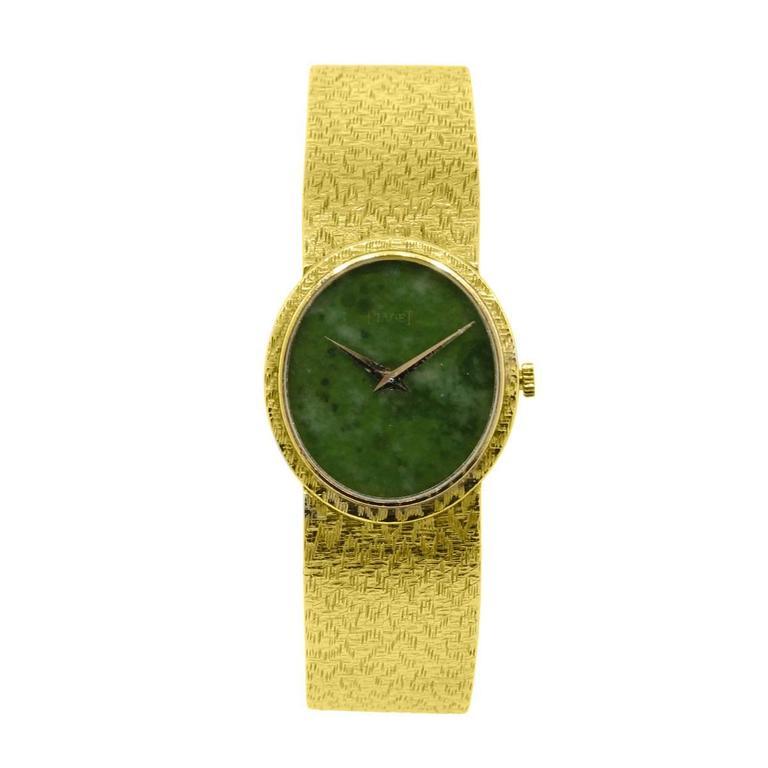 Brand: Piaget Style: 18k Yellow Gold Jade Stone Dial Ladies Watch Case Material: 18k Yellow Gold Dial: Green Jade stone dial Bezel: 18k Yellow Gold bezel Case Measurements: 25mm X 27mm Bracelet: 18k Yellow Gold Clasp: Jeweler's Clasp Movement: Hand