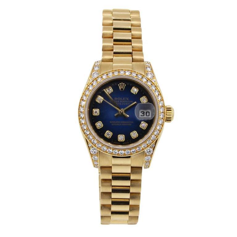 Brand: Rolex MPN: 179158 Model: Datejust Presidential Case Material: 18k Yellow Gold Case Diameter: 26mm Bezel: Diamond bezel (factory) Dial: Blue Vignette Diamond Dial with gold sticks and diamond hour markers; Date at 3 o'clock (factory) Bracelet
