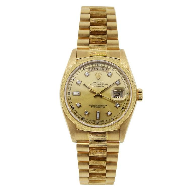Brand: Rolex Style: Rolex Day Date MPN; 18078 Serial #: 6 mill Case Material: 18k Yellow Gold Case Diameter: 36mm Bezel: 18k Yellow Gold fixed Bark bezel Dial: Champagne Diamond Dial with gold hands and diamond hour markers Bracelet: 18k Yellow Gold