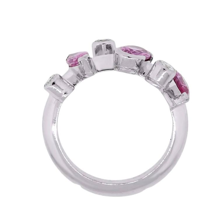 Designer: Cartier Material: Platinum Diamond Details: Approximately 0.24ctw of round brilliant diamonds. Diamonds are F/G in color and VS in clarity. Gemstone Details: 1 oval, 1 pear shape, 1 marquise shape pink sapphire. Ring Size: 4.25 Ring