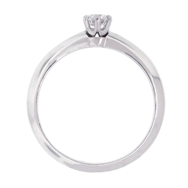 "Designer: Tiffany & Co. Material: Platinum Diamond details: Approximately 0.21ct round brilliant diamond. Diamond is G/H in color and VS in clarity. Ring Size: 6 (can be sized) Total Weight: 3.3g (2.2dwt) Measurements: 0.95"" x 0.20"" x"