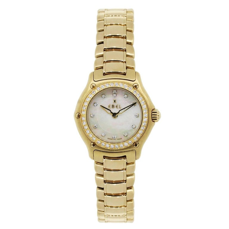 Brand: Ebel MPN: 80901214 Model: 1911 Case Material: 18k yellow gold Case Diameter: 26mm Crystal: Sapphire crystal Bezel: Diamond bezel Dial: Mother of pearl diamond dial with gold hands Bracelet: 18k yellow gold Size: Will fit a 6″ wrist Clasp: