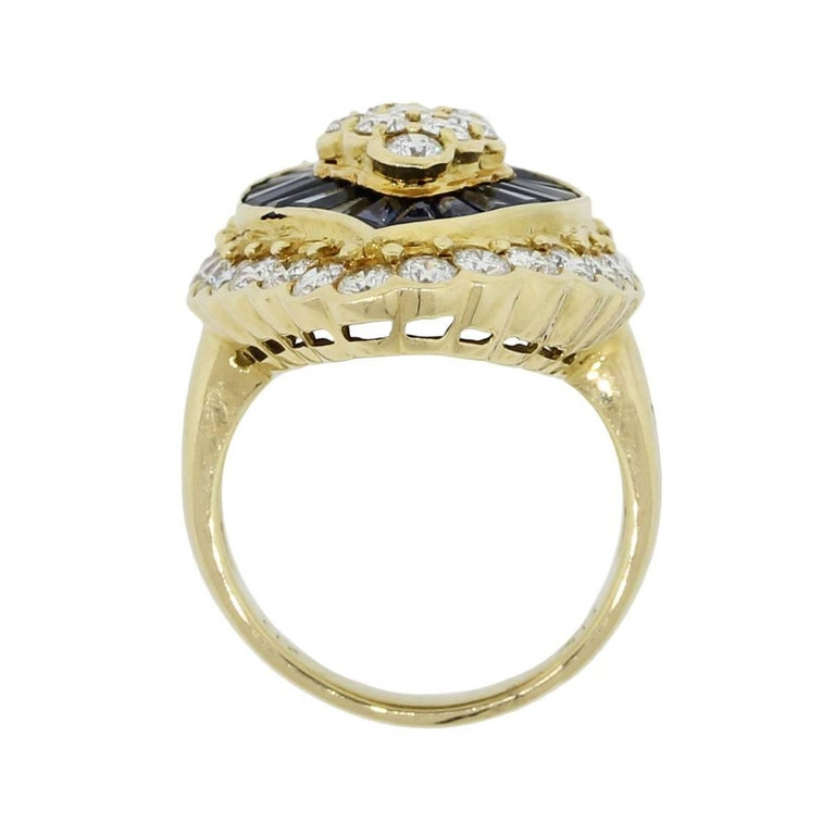 Material: 18k yellow gold Diamond Details: Approximately 3.67ctw of round brilliant diamonds. Diamonds are G/H in color and SI in clarity. Gemstone Details: Approximately 2.13ctw of baguette shape sapphires Ring Measurements: 1.18″ x 1.12″ x