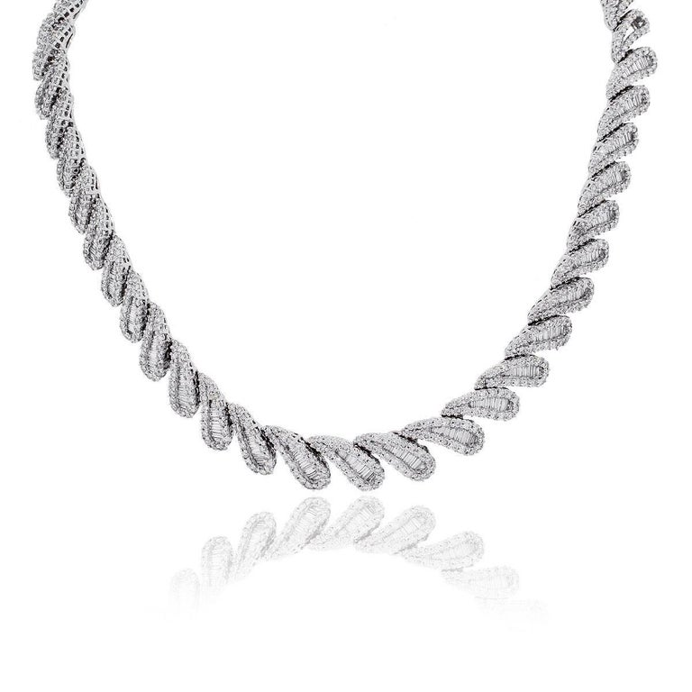 Style: Platinum Diamond Collar Necklace Material: Platinum Total Weight: 120g (77.2dwt) Diamonds: Approximately 20.34ctw of baguette and round brilliant Diamonds. Diamonds are G/H in color and VS in clarity. Measurements: 15″ x 0.47″ x 0.14″ SKU: