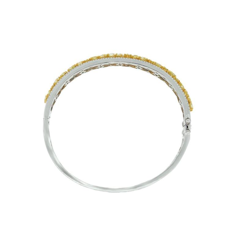 Style- 18k White Gold 5.53ctw Fancy Yellow Diamond Bangle Material- 18k White Gold with 18k Yellow Gold setting Diamond Details- Approximately 5.53ctw of Fancy Yellow Diamonds. Diamonds are natural in color and VS in clarity.  Approximately 0.93ctw