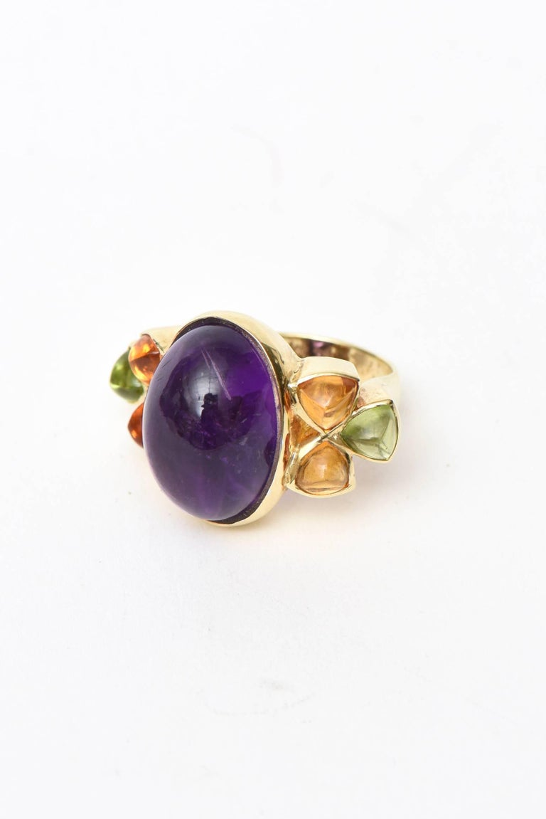 This colorful and lovely cocktail ring/ ring can be worn day to evening.It has a large amethyst stone in the center and is surrounded on either side by citrine and peridot. It is one oval cabochon cut amethyst that measures approx. 18.00 x 12.50 mm.