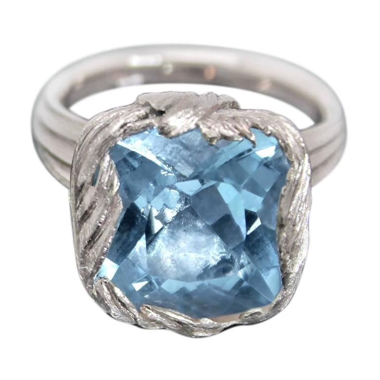 Aquamarine Cushion Cut stone set with a wrap of hand carved feathers, mounted to a grooved tapered ring shank. William Cheshire wanted to create a large but delicately made ring with an organic feel. The gentle feathers create the setting as they