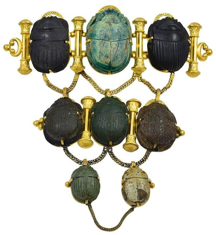 The 8 Scarabs, some of which are ancient, are arranged in three graduating rows and measure in length from 2.5cm to 1.5cm. Two have readable hieroglyphics and the other 6 have Scarab carapace reverses and the 6 Gold columns resemble the Temple