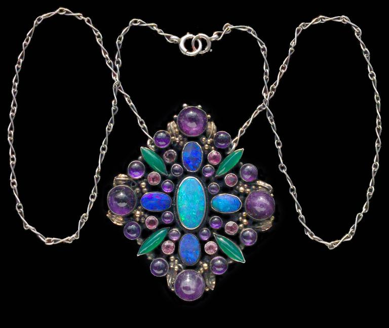 An impressive Arts & Crafts pendant with a sumptuous collection of gemstones.