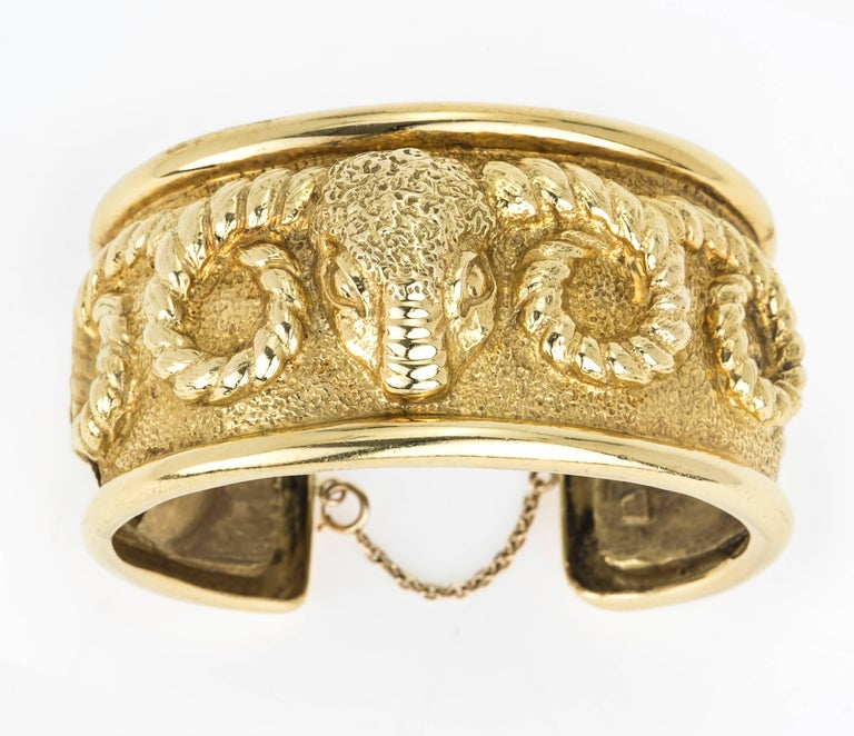 18k yellow gold clip on cuff bracelet with safety chain. Very handsome bold Aries  rams head relief cast of curly horns around the bracelet.  Hinge clip opens for easy wearing. Total weight: 94.5 gm. Hallmark in the back.