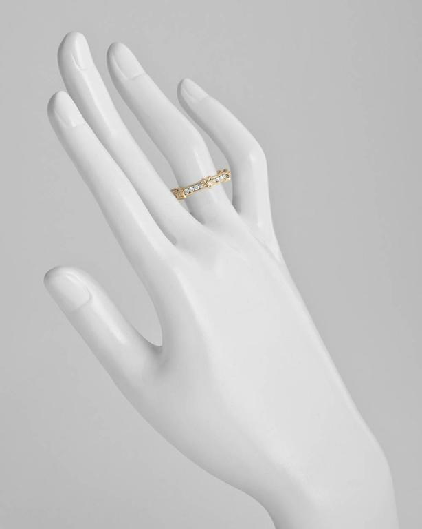 Band ring, designed as round-cut diamond-set eternity band with six gold star motifs each centering a round-cut diamond, in 18k yellow gold, numbered 21109, signed Chanel. Diamonds weighing approximately 1.00 total carats. Size 5.25.