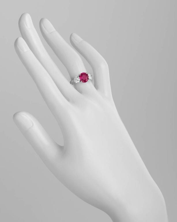 Burmese ruby and diamond three-stone ring, centering an oval-shaped ruby weighing 2.05 carats, with two round brilliant cut diamond shoulders weighing approximately 1.09 total carats and partway bead-set diamond band, mounted in platinum.