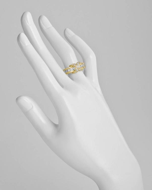 Band ring, centering a round-cut diamond-set 'X' motif, flanked by a row of channel-set square-cut diamonds, in 18k yellow gold, signed Tiffany & Co. Accompanied by Tiffany ring box. Size 5.75.