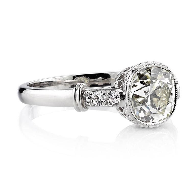 1.57ct OP/VS1 EGL certified vintage Cushion diamond set in a handcrafted platinum mounting. A classic solitaire design featuring a detailed gallery, bezel set diamond, and architectural elements.