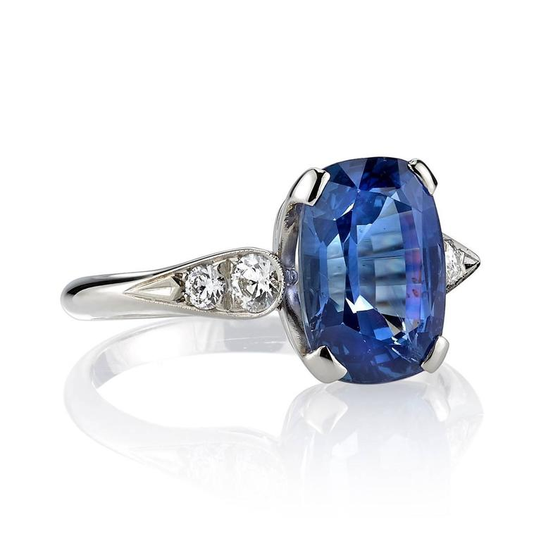 3.77ct Cushion cut Sapphire set in a handcrafted 18k white gold mounting. A classic design featuring a prong set diamond and a tapering band.