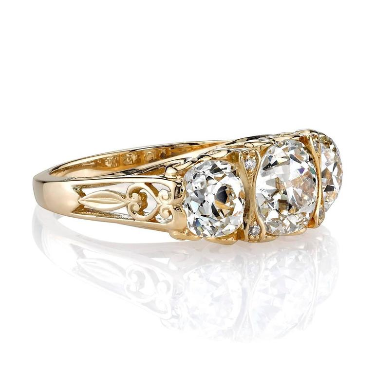 1.47ct J/SI2 vintage Cushion cut diamond with 1.54ctw vintage cushion cut accent stones set in a handcrafted 18K yellow gold three stone mounting. This ring features beautiful scroll work and intricate side detail.