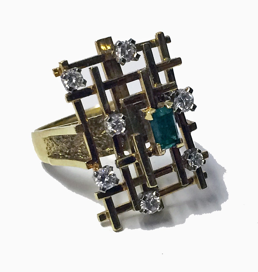 English 18ct, Emerald and Diamond Ring, C.1970. The ring of rectangular abstract design offset  in the centre with a small step cut slightly bluish Green emerald, the setting of three dimensional open bar design interspace with seven small full cut