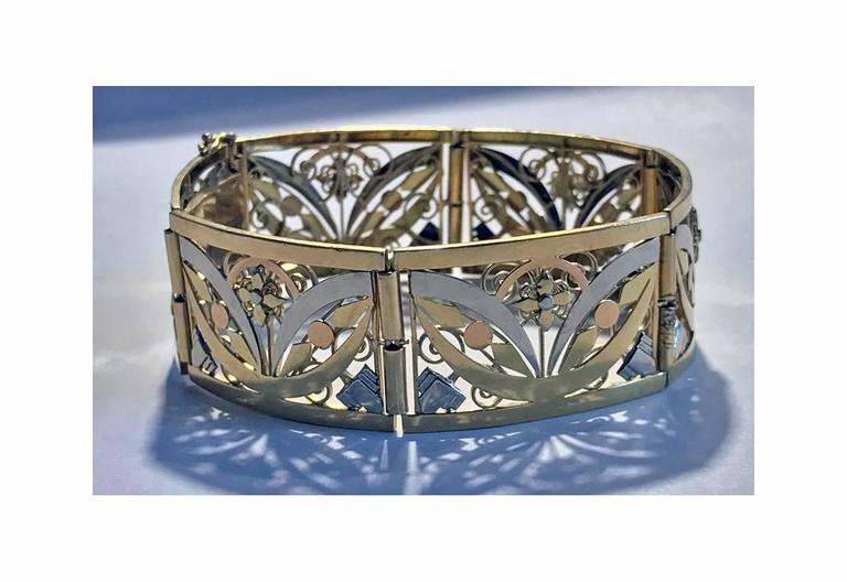 French 18K Art Nouveau three colour gold Bracelet, C.1900. The bracelet with six slightly convex pierced open stylised foliate hinged sections, terminating with tongue and box clasp fastener, safety catches attached. French marks and maker's mark SR