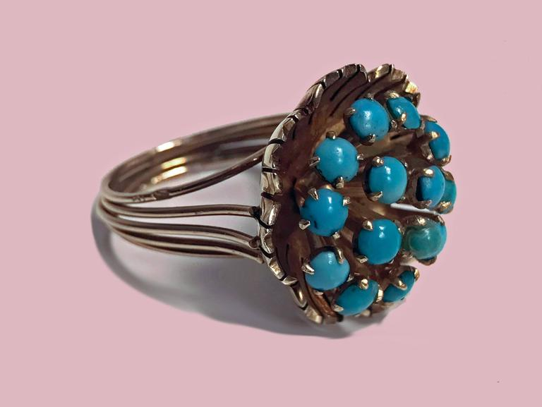 14K Turquoise Cluster Ring, butter cup design, C.1960. The large cluster set with 14 cabochon turquoise, gauging 3.00 to 3.50 mm, greenish blue, slight variance in stones, all claw set within a buttercup design, split gold wire shank. Stamped 14K