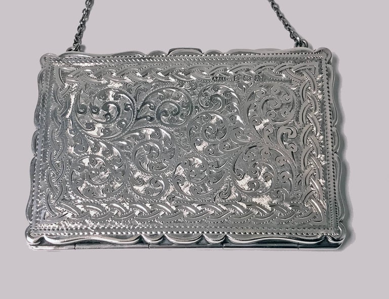 Antique Silver Card Case in form of purse, Birmingham 1910, Adie & Lovekin Ltd. The case of hinge and thumb piece design, richly engraved scroll foliage decoration, light monogram possibly MJ. Measures: 3.75 x 2.625 inches (excluding chain). Weight:
