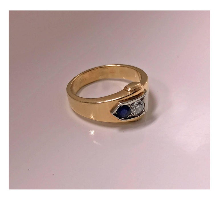 Sapphire and Diamond Ring mounted in 18K and 10K Gold, 20th century. The Ring of a buckle design, the `clasp set with a round european cut diamond, approximately 0.20 ct, approximately SI clarity, approximately I colour and round facetted medium,