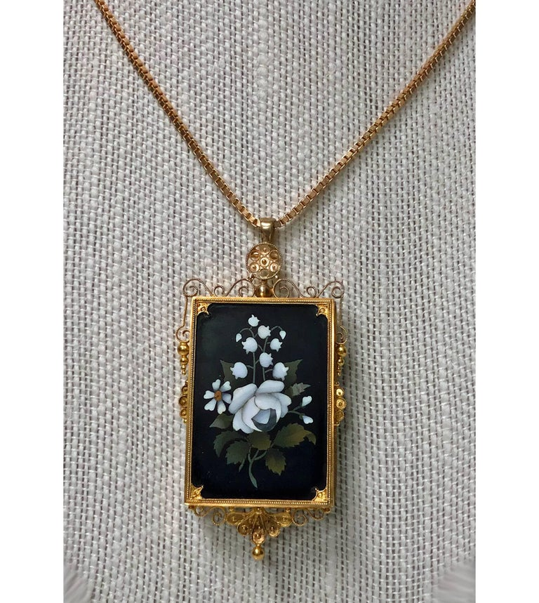 Antique Gold Pietra Dura Pendant Brooch, Italy C.1875. The Pendant Brooch of rectangular shape, fine pietra dura floral white rose inlay, the surround gold mount of scroll granular etruscan work. Gold pin to reverse and later hinged bale pendant.