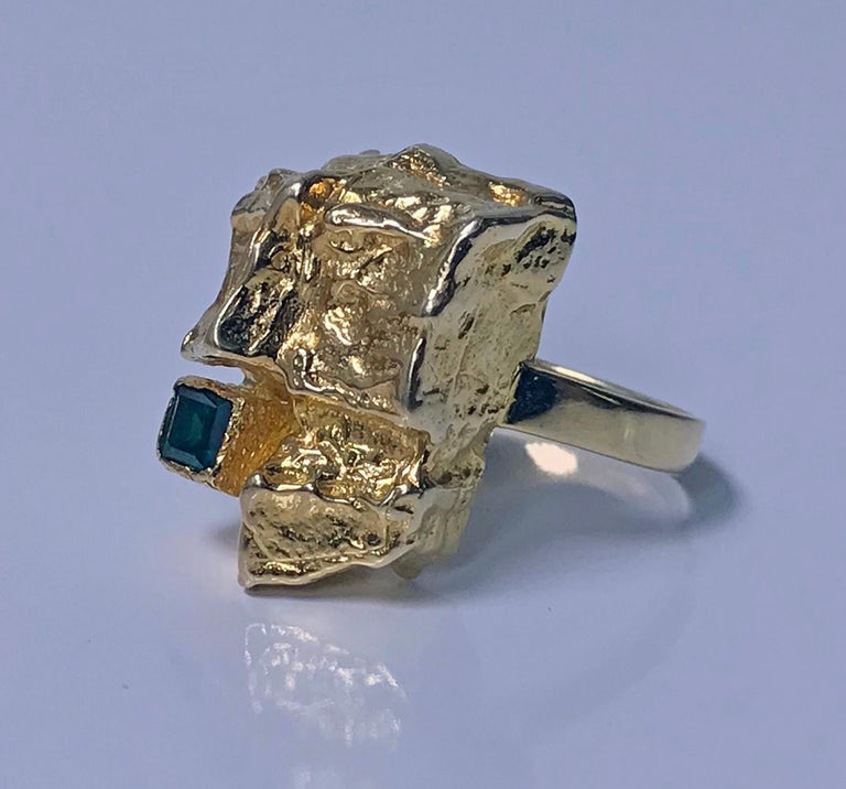 1970's Scandinavian Gold and Emerald abstract Ring. The Ring of large textured abstract gold nugget form set in the corner with a slightly bluish Green square cut emerald, approximately 0.30 ct, approximately VS clarity (type 111), plain polished