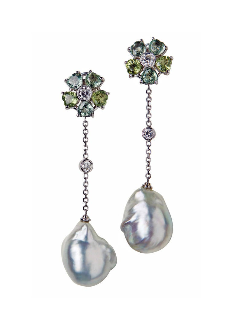 Pair of 18K, Diamond, & Baroque Pearl drop Earrings. Each suspending a fine silver white south sea baroque pearl, gauging approx 18 x 15 mm, central drop section bezel set with a small round cut diamond, suspended from claw set diamond and green