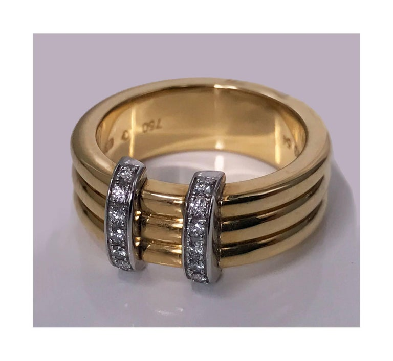 Omega 18K yellow Gold three band Ring. The Ring with two horizontal sections set with round brilliant cut diamonds, total diamond weight approximately 0.15ct, average VS-SI clarity, average I colour. French marks. Ring Size: 6 Item Weight: 12.55