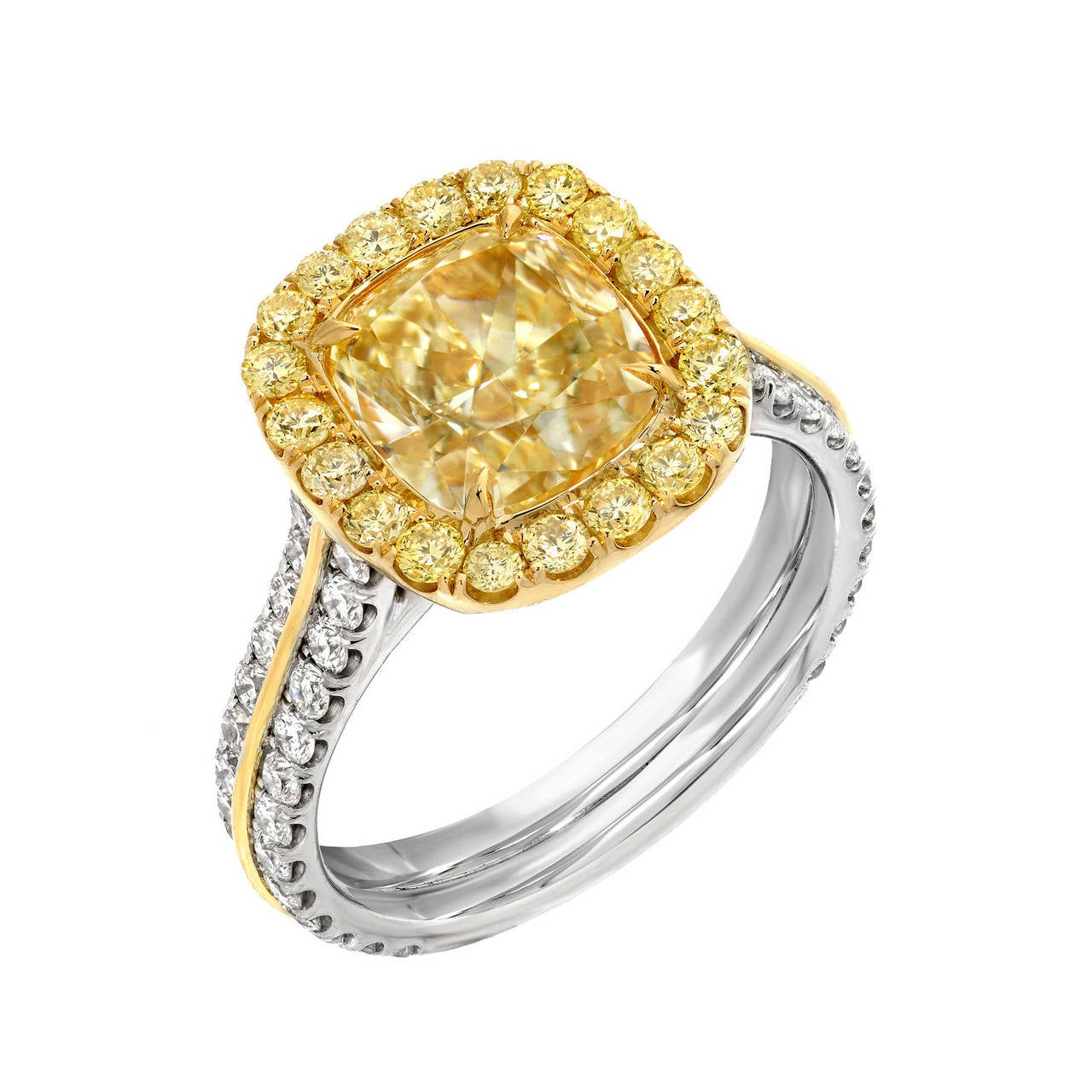 Platinum and 18K yellow gold ring, set with a supreme, G.I.A certified, 2.40 carat Fancy Light Yellow diamond cushion cut, VS2 clarity, surrounded by fancy yellow diamond rounds totaling 0.37 carats, and accented by round white diamonds totaling