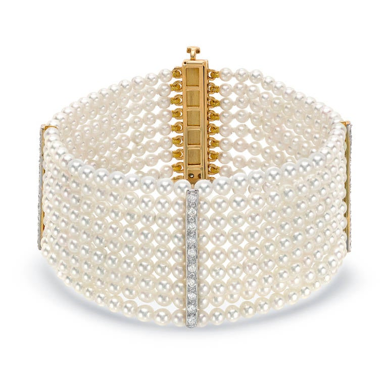 Pearl bracelet comprised of 9 rows of hard-to-find 3mm-3.5mm Japanese Akoya Pearls, complimented by a total of 1.15ct diamonds set on the dividing bars and clasp. Crafted in 14K gold. The length of the bracelet is approx. 7 inches and the width is