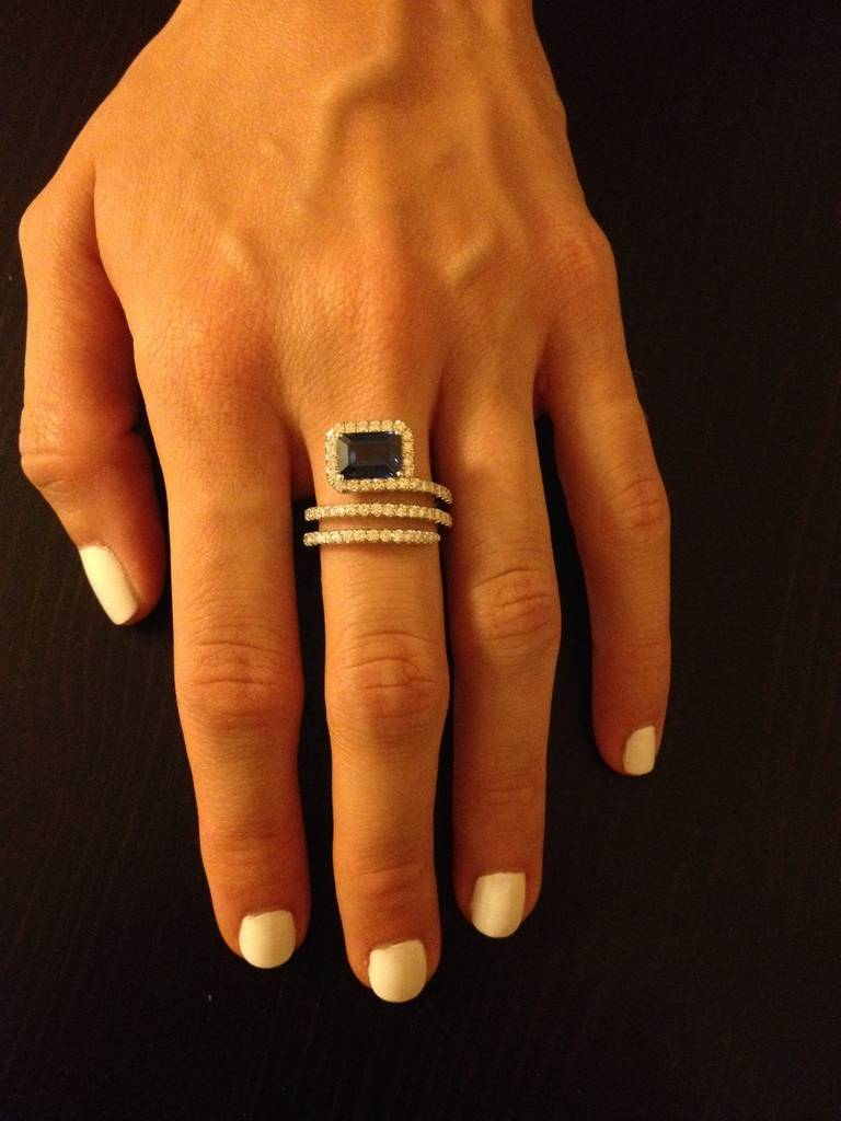 A swirl of 0.83ct diamonds curls three times around the finger, leading to a 2.04ct emerald-cut Royal Blue Sapphire set at the bottom of the ring, framed in diamonds.  Crafted by hand in 18K white gold. Size 6.5.