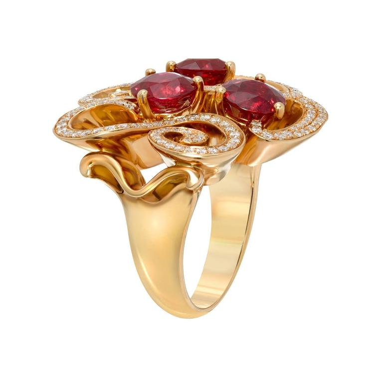 An exceptional trio of Burma Rubies, weighing a total of 3.82 carats, are surrounded by a total of 0.49 carat round brilliant diamonds, in this magnificent 18K yellow gold ring. Size 5.75. Re-sizing is complimentary upon request.